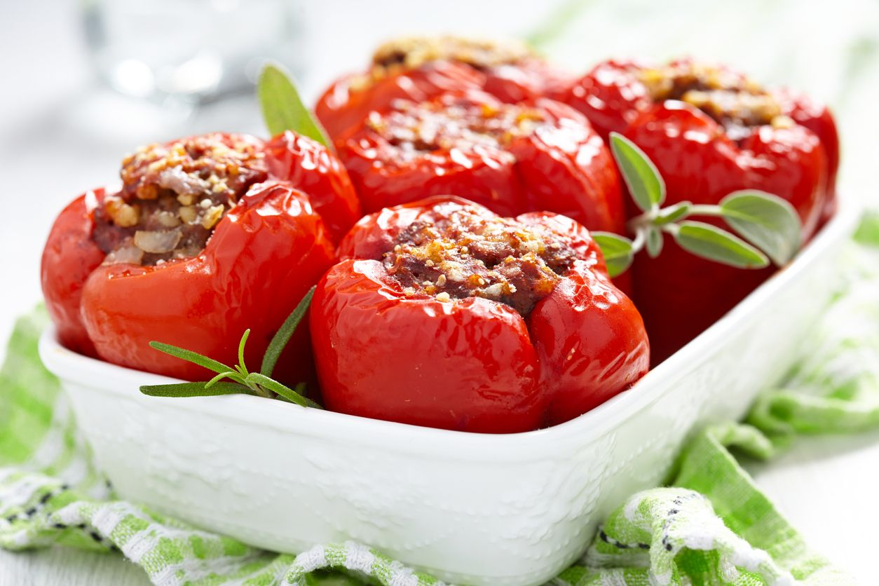 Traditional stuffed bell peppers with tomato sauce and infused rice